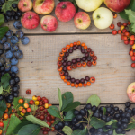 """Frame of fruits and berries with """"E"""" letter on a wooden background"""
