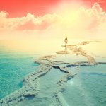 Silhouette of young woman walking on Dead Sea salt shore at sunrise towards the sun. Gradient color. Red dramatic sky.