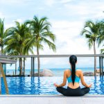 Fit woman sitting in yoga pose by pool