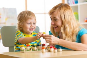 Mom at table with toddler and building blocks